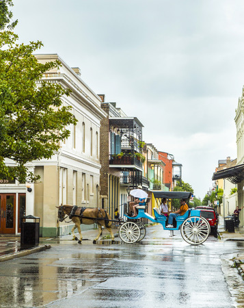 NEW ORLEANS - JULY 15, 2013: people do a horse coach trip in the old french Quarter in New Orleans.