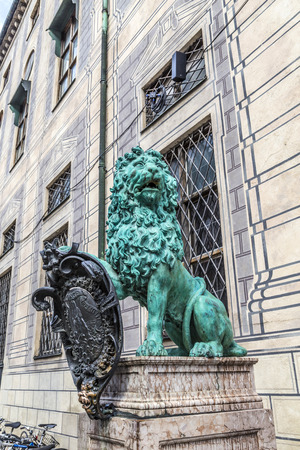 oxidated: bavarian lion statue in front of residence palace at odeonsplatz, old town munich. Selective focus.