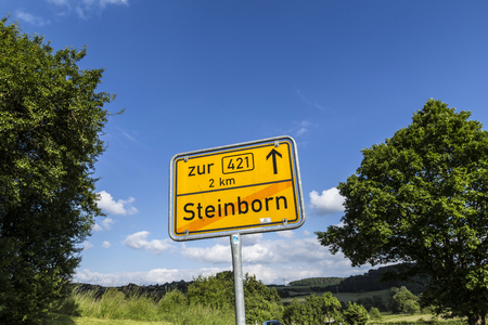 city limit: STEINBORN, GERMANY - JUNE 19, 2016: town sign Steinborn with red diagonal stripe indicates end of Steinborn village in the Eifel, Germany,