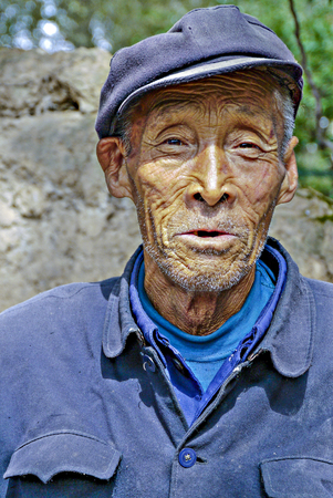12 class: GUEILLIN, CHINA - SEP 12: very old farmer in traditional blue working class uniform on Sep 12, 2011 in Gueillin, China. Farmer earn less than 30 percent than people with office jobs.