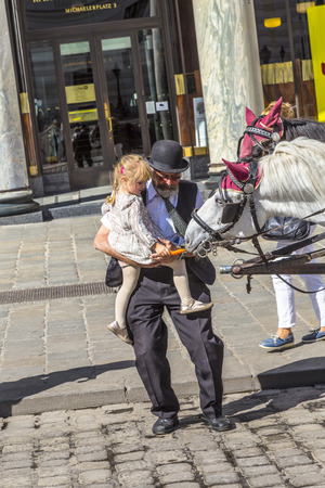 coachman: VIENNA, AUSTRIA - APR 27, 2015: coachman of traditional horse riding in vienna helps a young girl to feed the horses.  The number of horse riders is limited and they have a special licence.