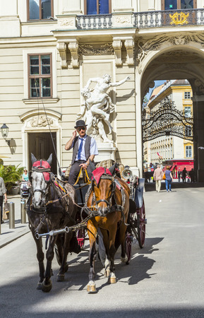 solder: VIENNA, AUSTRIA - APR 27, 2015: Traditional horse riding in a Fiaker through the city center in Vienna, Austria. The numer of horse riders is limited and they have a special licence. Editorial