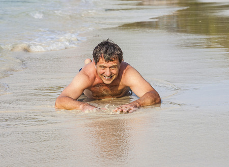 bathingsuit: Man in bathingsuit is lying at the beach and enjoying the saltwater with tiny waves and smiles Stock Photo