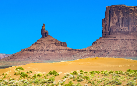 butte: famous butte in monument valley under blue sky