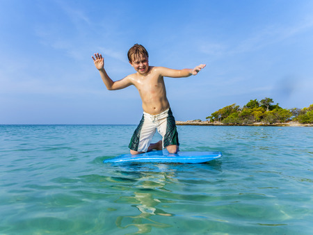 boy surfing on a small surfboard , his brother holds the surfboard on his back