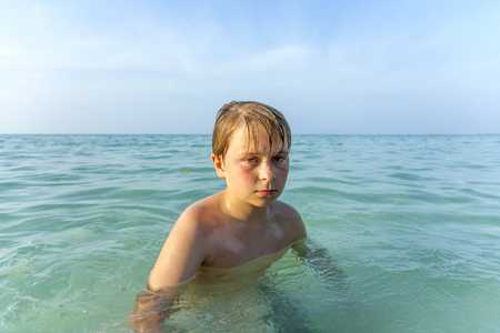 angry young boy is walking in the clear warm saltwater at the beautiful beach