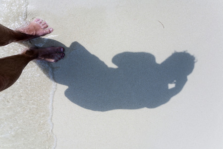 adult footprint: man is throwing shadow to the fine sand of the beach, showing the complete body in a smoth circle