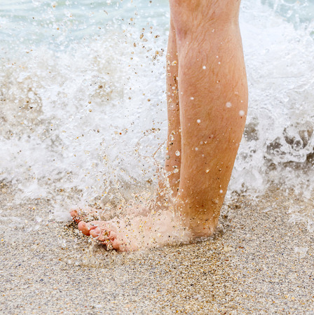 feet of boy running along the beach in the water Stock Photo