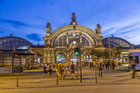 describes: FRANKFURT AM MAIN, GERMANY- AUG 28, 2016: people in front of Deutsche Bahn railway central station (Hauptbahnhof). Deutsche Bahn describes itself as the second-largest transport company in the world