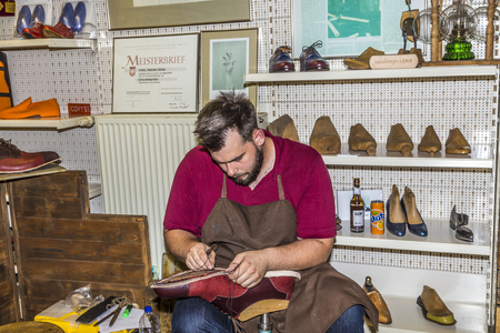 he is a traditional: FRANKFURT, GERMANY - SEP 8, 2016: the shoemaker opens his shop at the annual Bahnhofsviertel party in Frankfurt. He shows the traditional handcraft how to make shoes. Editorial