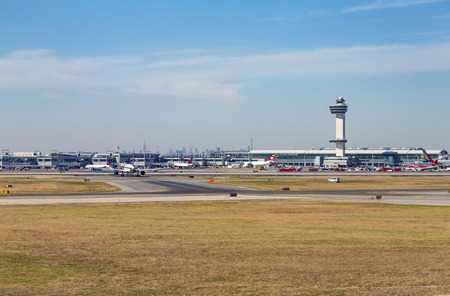 NEW YORK, USA - OCT 20, 2015: Air Traffic Control Tower and Terminal 4 with Air planes at the gates in JFK Airport in NY. 1963 the airport was rededicated John F. Kennedy International Airport.
