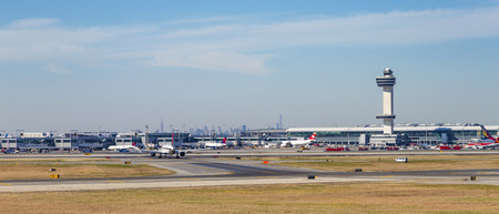 Kennedy: NEW YORK, USA - OCT 20, 2015: Air Traffic Control Tower and Terminal 4 with Air planes at the gates in JFK Airport in NY. 1963 the airport was rededicated John F. Kennedy International Airport.