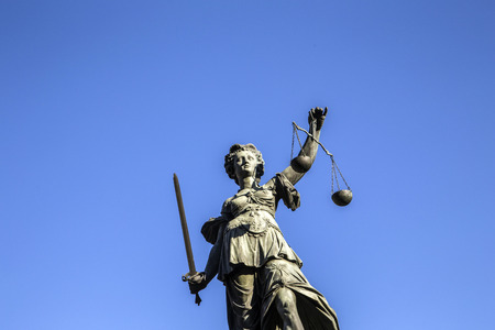 justitia: Justitia - Lady Justice sculpture on the Roemerberg square under blue sky Stock Photo