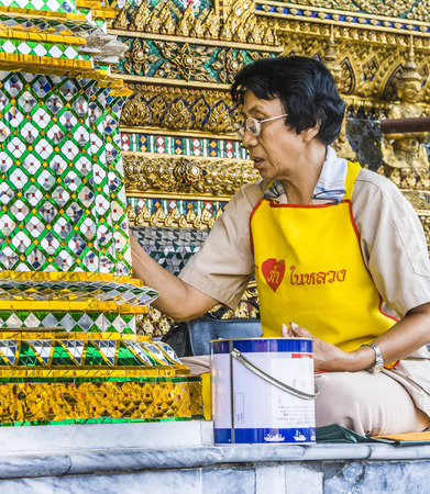 permanently: BANGKOK, THAILAND - DEC 26, 2007: woman is restoring a mosaique at the wall in the grand palace in Bangkok, Thailand. There are permanently working more than 300 people for keeping the temple in good condition.