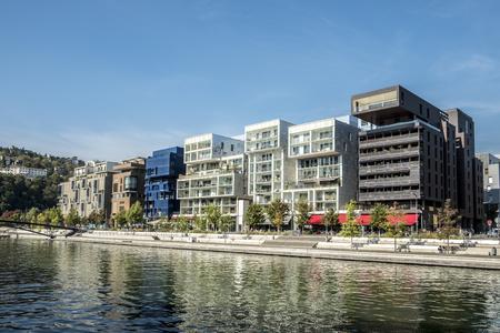 LYON, FRANKREICH - 28. SEPTEMBER 2016: Leute in berühmtem Confluence-Bezirk in Lyon, Frankreich mit Fluss. Dieses Gebiet war ein ehemaliges Industriegebiet und wird in ein neues modernes Viertel umgewandelt.