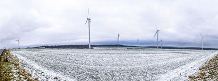 covered fields: wind generators in Thuringia with snow covered fields and cloudy sky