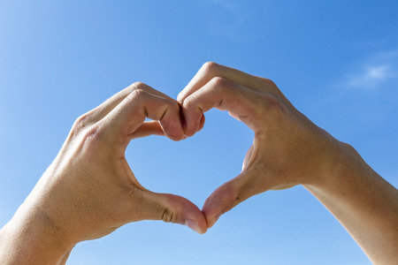under heart: heart shape with hand under blue sky in sun Stock Photo