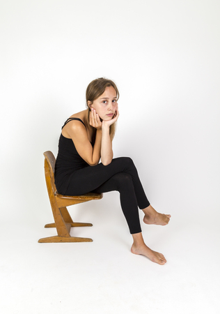 young beautiful girl with brown hair sits on an old school chair