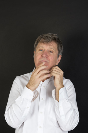 snotty: portrait of mature man in white business shirt looking snotty Stock Photo