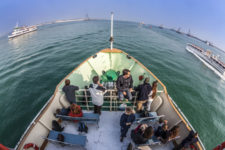 VENICE, ITALY - APR 10, 2007: people on a boat from at the way to Venice. Several ferries serve the smaller islands in the lagoon.