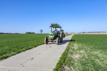 ESCHBORN, GERMANY - APR 17, 2010: farmer on his tractor rides back after plowing his field. He drives an old Fendt tractor. Editorial