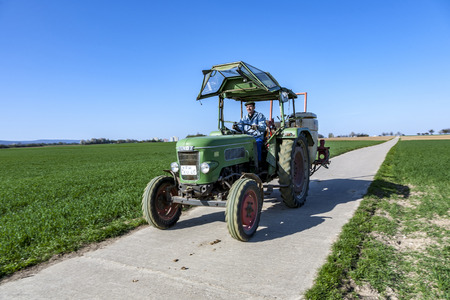 he old: ESCHBORN, GERMANY - APR 17, 2010: farmer on his tractor rides back after plowing his field. He drives an old Fendt tractor. Editorial