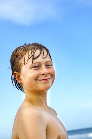 portrait of happy caucasian teenage boy at the beach