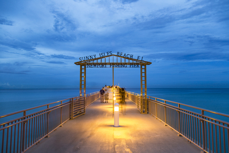 SUNNY ISLES BEACH, USA - AUG 5, 2013: newport fishing pier by night with shadows of people. The pier was reopened in 2013 after restoration and renovation.