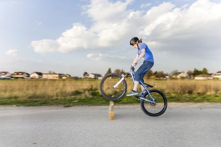mit: Jugendlicher übt Tricks, Sprünge mit dem Bike auf der Strasse Stock Photo