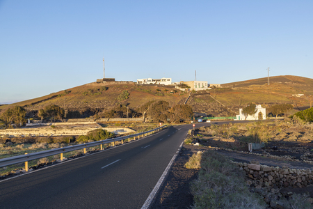 road in hilly area with farm houses in Lanzarote in sunrise