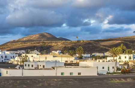 View on traditional whitewashed village with volcanos on the background in the morning on Lanzarote island in Spain
