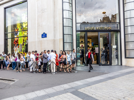 PARIS, FRANCE - JUNE 12, 2015: people queue up in front of Louis Vuitton shop at champs elysees for shopping.