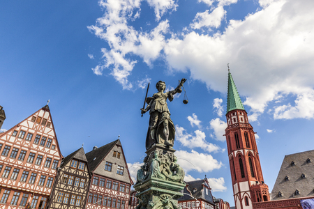 roemerberg: lady Justice at roemerberg in Frankfurt with half timbered houses and Nicolai church under blue sky Stock Photo