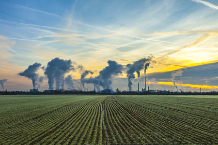 chimneys and smoke of industry plant with fields in sunrise Stock Photo