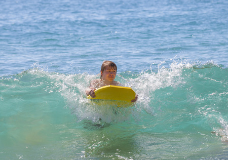 boy has fun surfing in the waves in Lanzarote 免版税图像