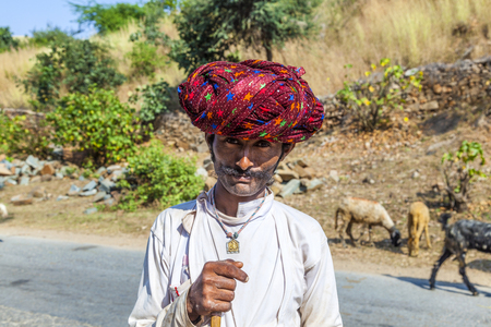 PUSHKAR, INDIA - OCT 22, 2012: goatherd moves with his goats to the next ground near Pushkar, Rajasthan, India.  Goats are the main source to earn money for the villagers in the Marwari region. Editorial