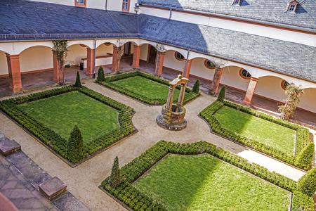 hessen: SELIGENSTADT, GERMANY - MAR 4, 2017: famous benedictine cloister in Seligenstadt, Germany under blue sky with cloister garden.