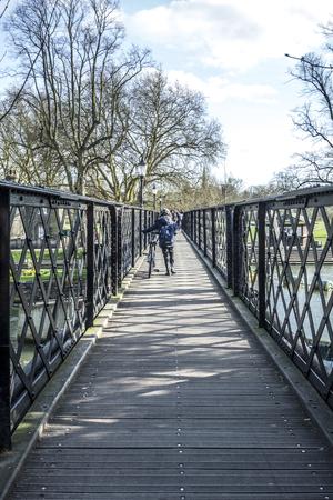 britan: CAMBRIDGE, ENGLAND - MAR 13, 2017: people crossing the river cam at an old iron pedestrian bridge.