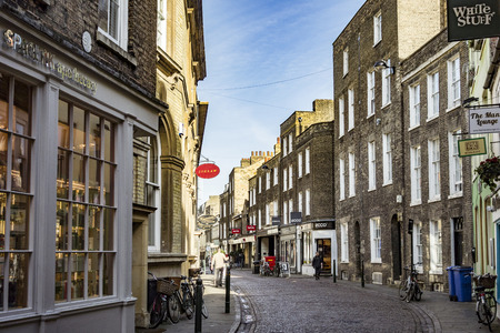 britan: CAMBRIDGE, ENGLAND - MAR 13, 2017: typical street scene in the old part of Cambridge. The streets are still covered by cobble stones.