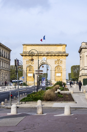 triumphe: MONTPELLIER, FRANCE - MAR 31, 2017: Arc de Triumphe in Montpellier, dating from 1692, with surrounding buildings, people and traffic signs.