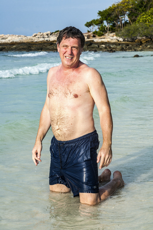 mature man enjoys the beautiful sandy beach