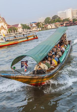 BANGKOK, THAILAND - JAN 4, 2010: people travel in the morning with longboats at the river Chao Phraya in Bangkok. The boats belong to Bangkok public transportation system.