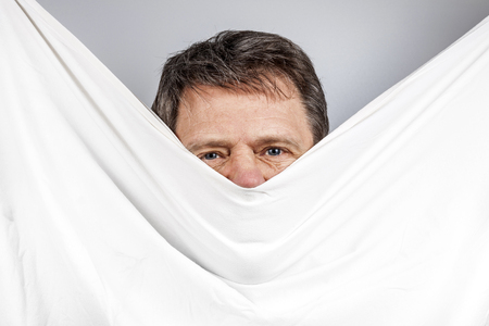 face of man partially covered by linen