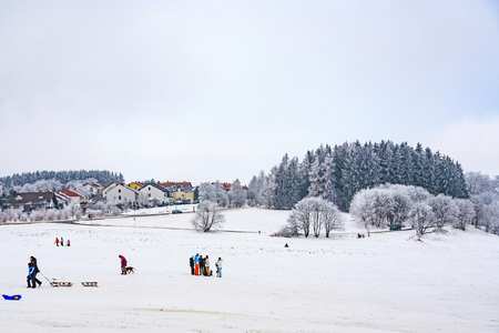 16: OBERREIFENBERG, GERMANY - JAN 16, 2010: children are skating at a toboggan run in winter on snow. Snow in this area is very seldom due to world wide encrease of temperature.