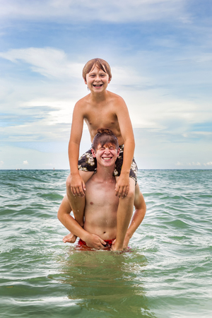 boys having fun in the beautiful clear sea by playing pickaback photo