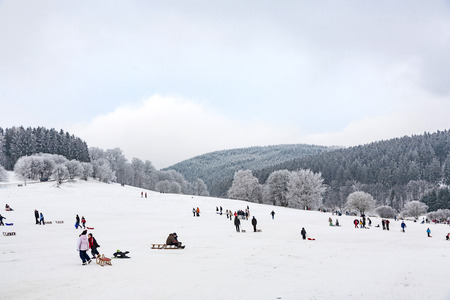 OBERREIFENBERG, GERMANY - JAN 16, 2010: children are skating at a toboggan run in winter on snow. Snow in this area is very seldom due to world wide encrease of temperature.