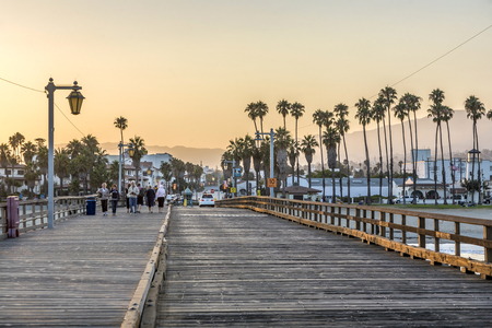 SANTA BARBARA, USA - JULY 28, 2008: people at scenic old wooden pier in Santa Barbara in sunset. The pier was completed in 1872 and was the longest pier at that time in the USA.