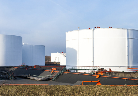 white tanks in tank farm with blue sky Imagens