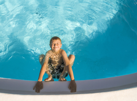 happy cute boy in swimming pool laughes and poses photo