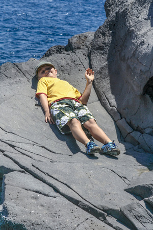 happy boy lies on the rock and is greating by raising the hand photo